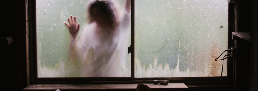 Woman in white trapped outside a frosted window as if trapped outside of her life.